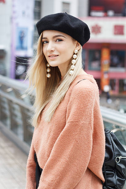 Beautiful woman in a pink sweater A beautiful young blonde woman dressed in a large warm pink sweater with a black beret and gorgeous earrings. She goes through a big spectacular Chinese city in autumn and enjoying every moment. beret stock pictures, royalty-free photos & images