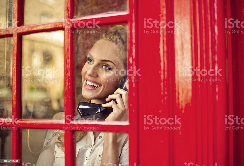 Beautiful woman in a red telephone booth royalty-free stock photo