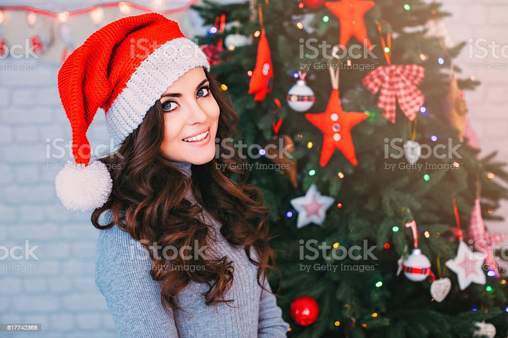 Beautiful woman in a Santa hat on Christmas background. stock photo