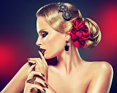 Retro style hairstyle,smokey eyeshadow and bright red lipstick on the face of young model. Elegant gesture of hands decorated by jewelry rings and black manicure.