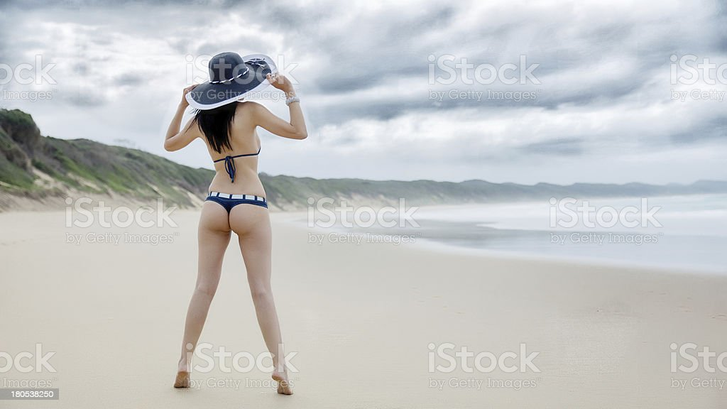 Beautiful woman in a thong on the beach stock photo