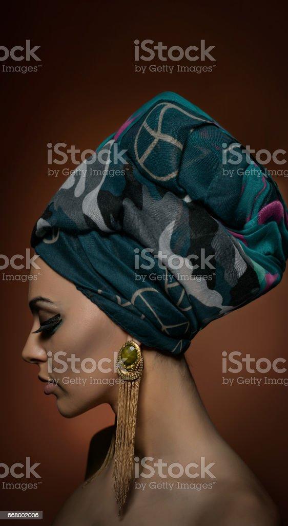 Schöne Frau in einem Turban. Junge schöne Frau mit Turban und goldenen Accessoires. Schönheit modische Frau mit Haaren in Turban gewickelt. Ziemlich kaukasischen Modell tragen Ohrringe posiert im Studio. – Foto