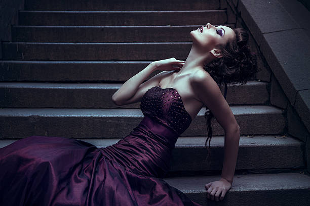 beautiful woman in a violet dress for photography - gothic fashion stock photos and pictures