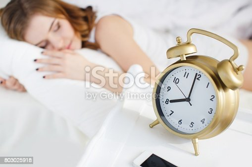 509031214istockphoto Beautiful woman in a white bed with a big alarm clock 803025918