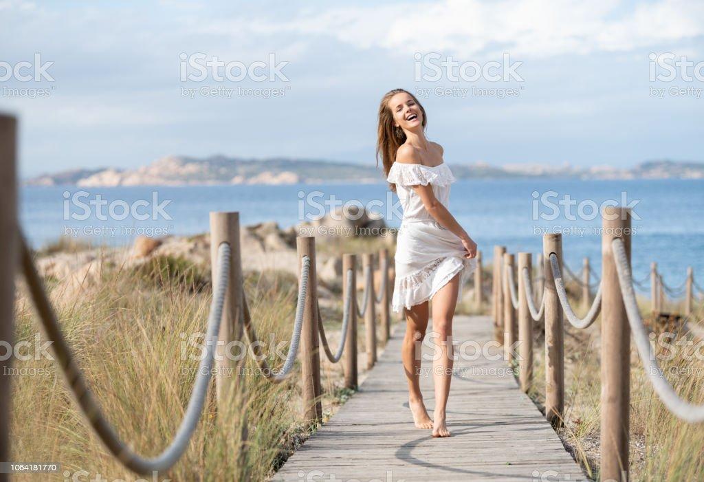 Schöne Frau in einem weißen Kleid mit einem perfekten offen Ausdruck hinunter eine Seilschaft Fußweg zum Strand, Sardinien, Italien – Foto