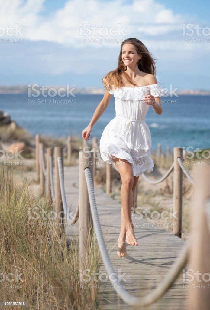 Schöne Frau in einem weißen Kleid mit einem perfekten offen Ausdruck springen hinunter eine Seilschaft Fußweg zum Strand, Sardinien, Italien – Foto