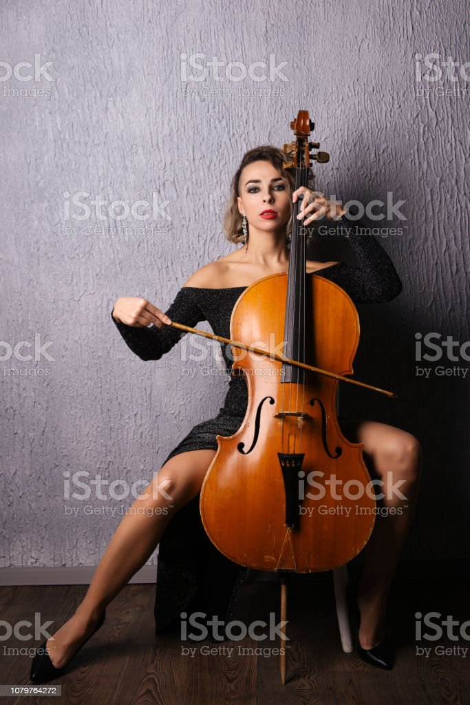 Beautiful woman in an evening dress playing the cello stock photo