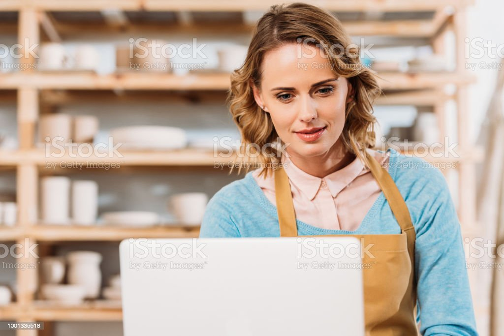 beautiful woman in apron using laptop in pottery workshop stock photo