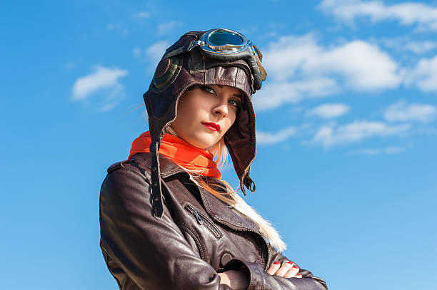 beautiful woman in aviator helmet on the sky background stock photo