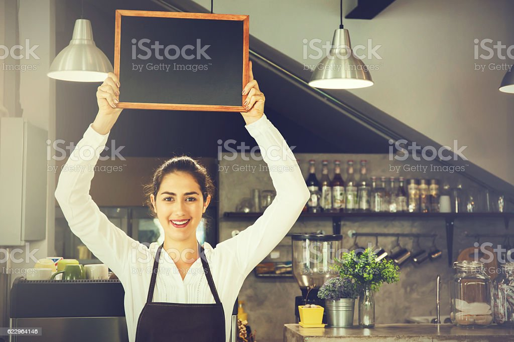 Beautiful woman in barista apron holding empty blackboard in cafe stock photo