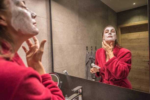Beautiful Woman in Bath Robe Putting a Mask on her Face During the Evening Routine in the Bathroom stock photo