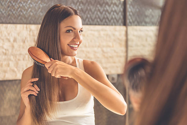 Beautiful woman in bathroom Beautiful young woman in white undershirt is combing her hair and smiling while looking into the mirror in bathroom combing stock pictures, royalty-free photos & images