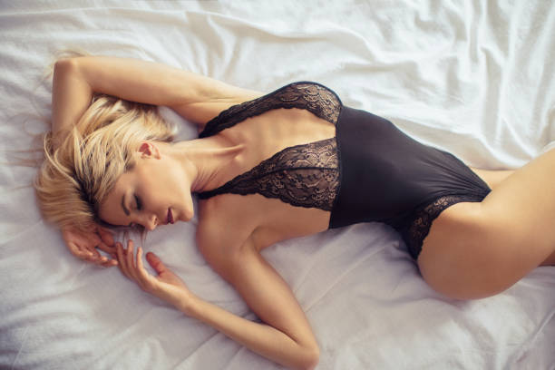 Beautiful woman in bedroom A pretty young blond woman enjoying in bed and wearing black bodysuit. She closed her eyes. lingerie stock pictures, royalty-free photos & images