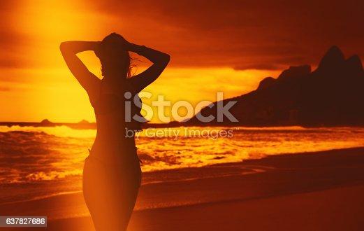 istock Beautiful woman in bikini at beach after swimming at sunset 637827686
