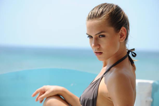 Beautiful woman in bikini is sitting on the deck chair on the beach stock photo