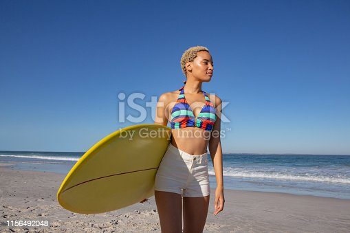 Front view of African american woman in bikini standing with surfboard on beach in the sunshine