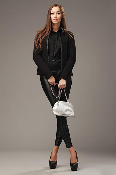 schöne frau in schwarzer kleidung mit silber mode tasche - leder leggings stock-fotos und bilder