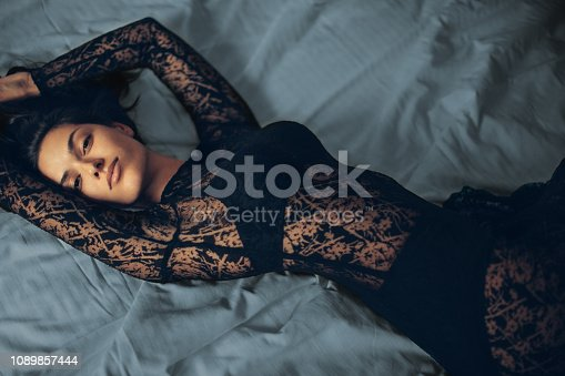 Very attractive young woman wearing black elegant dress and lying on bed