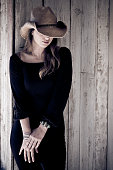 istock Beautiful woman in black dress with cowboy hat leaning 108196810