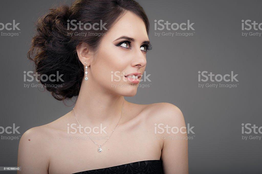Beautiful Woman in Black Evening Dress Wearing Jewelry stock photo