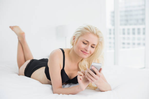 Beautiful woman in black lingerie text messaging in bed stock photo