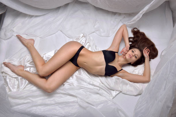 Cтоковое фото Beautiful woman in black underwear laying on the bed.
