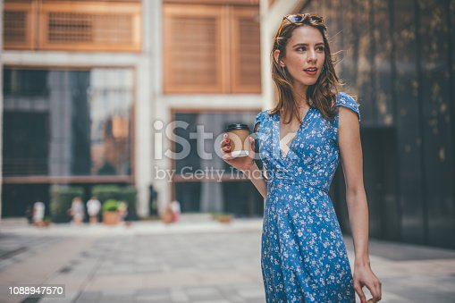 One woman, cute young woman in city, holding a coffee cup.