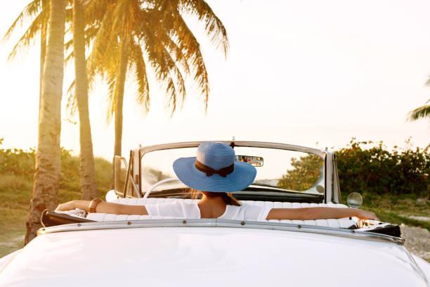 schöne frau in blauen hut und weißen retro-cabriolet - urlaub in kuba stock-fotos und bilder