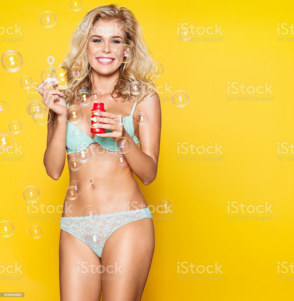 Beautiful woman in blue lingerie laughs and inflates soap bubbles stock photo