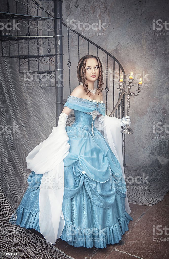 Beautiful woman in blue medieval dress with candelabrum stock photo