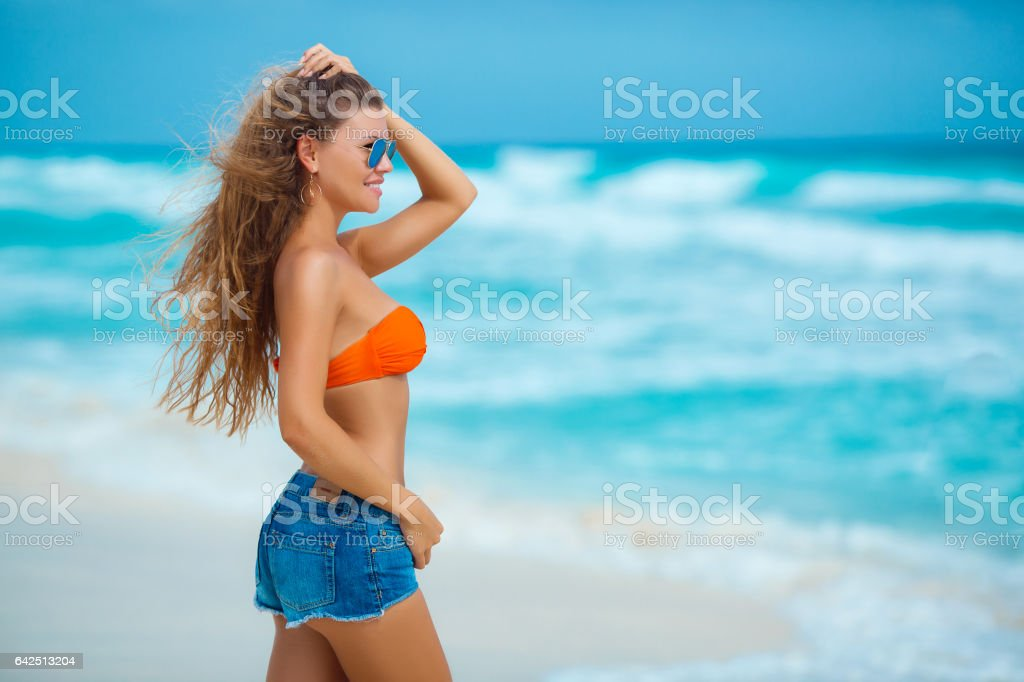Beautiful woman in blue shorts on a tropical beach stock photo