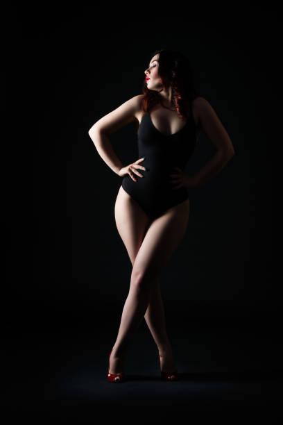 Hermosa mujer en mono posando sobre fondo negro, discreto estudio tiro - foto de stock