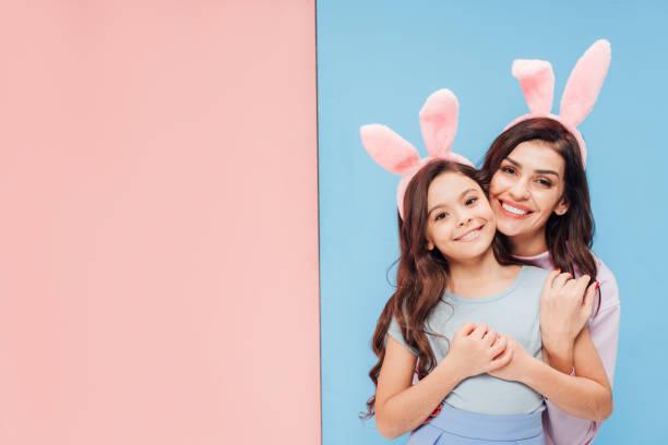 schöne Frau in Hasenohren Kind umarmt und lächelt in die Kamera auf blau und rosa Hintergrund – Foto
