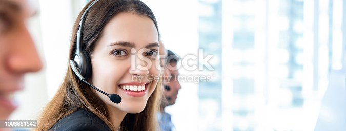 1142008983 istock photo Beautiful woman in call center banner gackground 1008681542