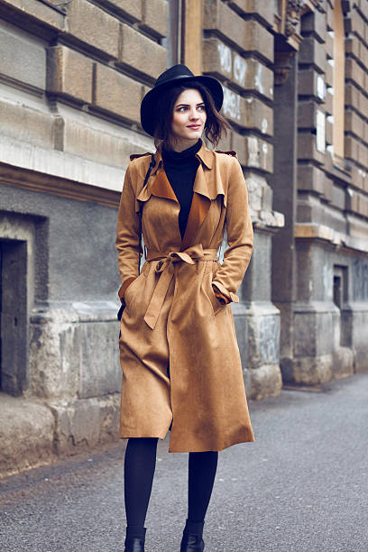 Beautiful woman in coat Young beautiful brunette walking and enjoying old city. She is wearing brown coat because is cold and her hands are in pocket. On head she has nice stylish black hat. As an addition she has black handbag. coat garment stock pictures, royalty-free photos & images