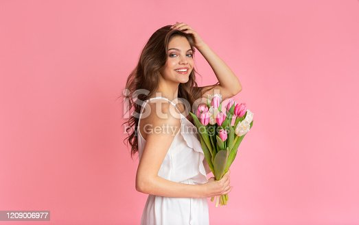 Portrait of beautiful girl in cocktail dress with tulips flower bouquet in hands over pink studio background, empty space