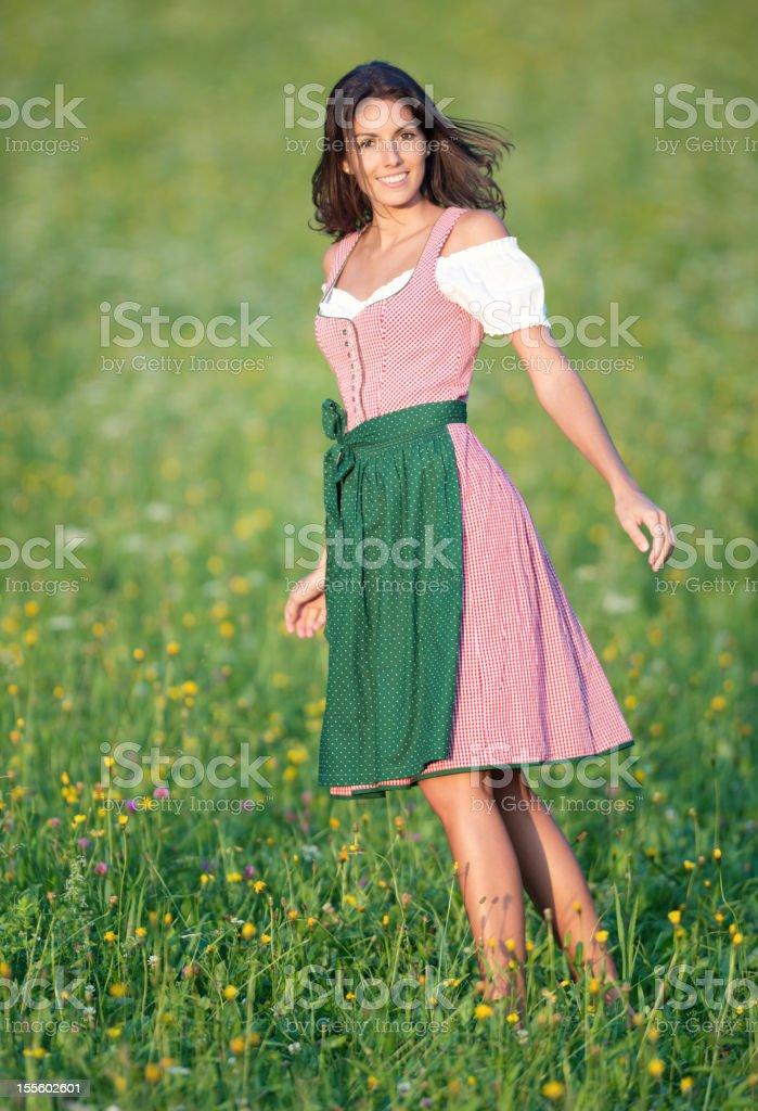 Beautiful woman in Dirndl Fashion dancing through the Meadows (XXXL) stock photo