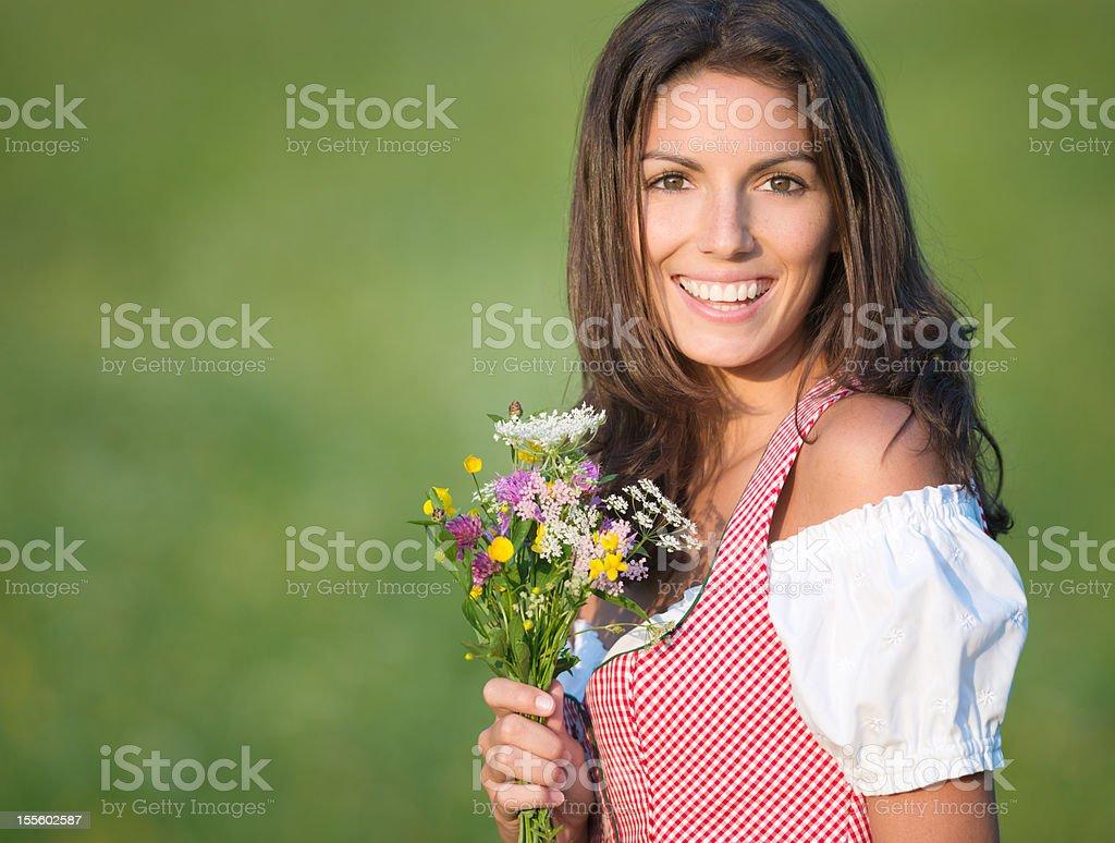 Beautiful woman in Dirndl Fashion holding a Flower Bouquet (XXXL) stock photo