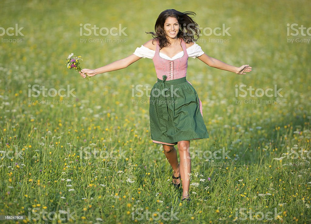 Beautiful woman in Dirndl Fashion running through the Meadows (XXXL) stock photo