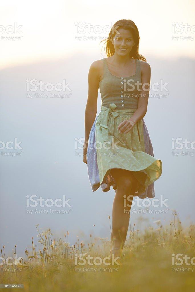 Beautiful woman in Dirndl Fashion running through the Meadows stock photo