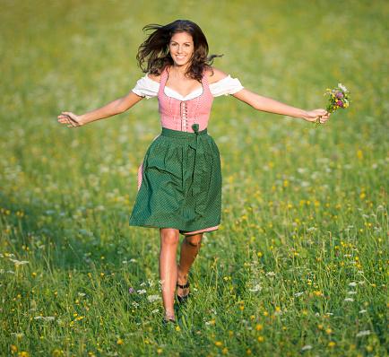 Beautiful woman in Dirndl running through the Meadows