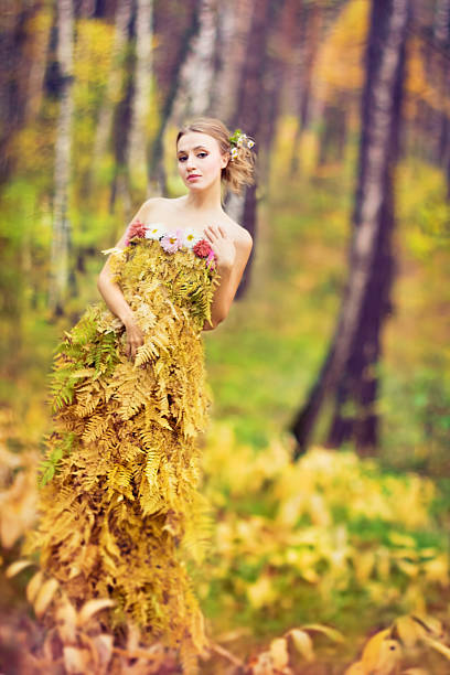 Beautiful woman in dress made with fern leaves. stock photo