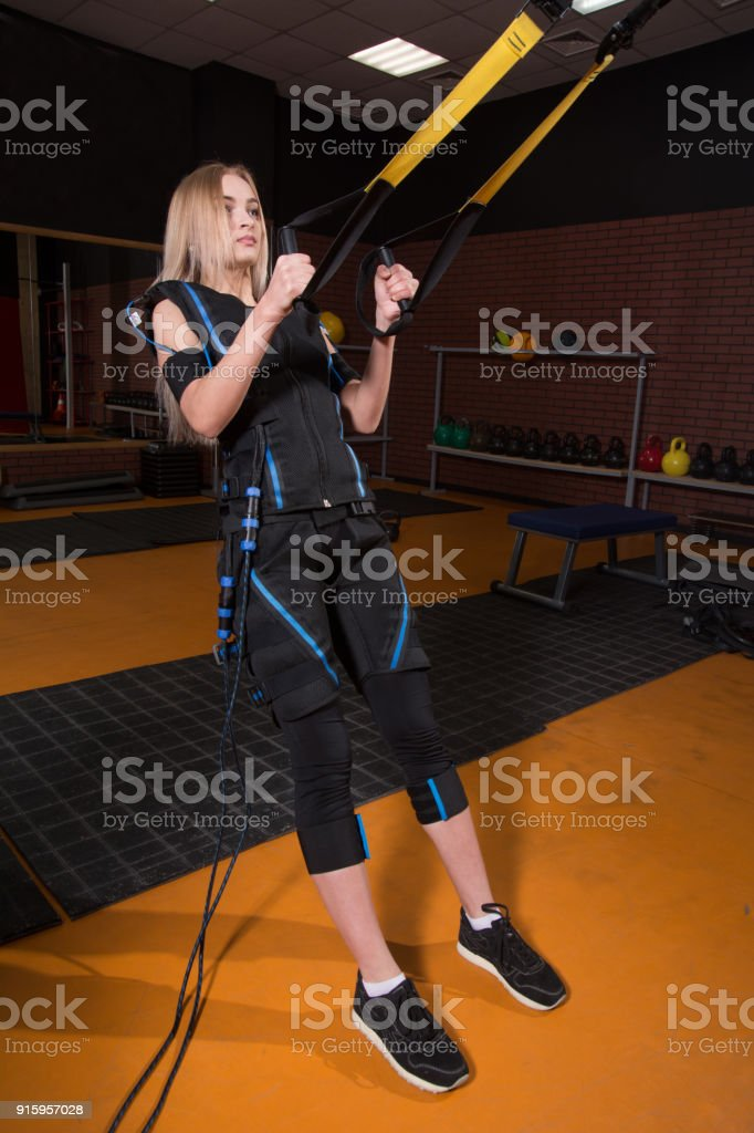 Beautiful woman in Electrical Muscular Stimulation suit doing squat exercise for back and with suspension stock photo