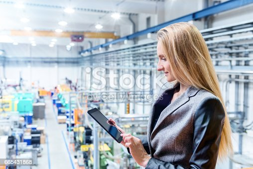 istock Beautiful woman in factory with digital tablet 665431868