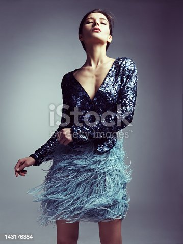 Studio portrait of fashionable woman in sequin jacket and skirt with feathers. Professional make-up and hairstyle.