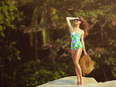Beautiful woman standing in front of the jungle. She's wearing floral swimsuit and holding straw hat in her hand.