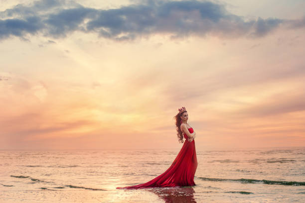 Beautiful woman in fluttering red dress on sea wave at sunset. stock photo