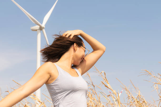 Beautiful woman in front of windmill. Environmental preservation people lifestyle. stock photo
