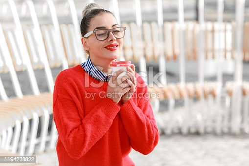 518885222istockphoto Beautiful woman in glasses, red sweater and red lipstick walking down the street with a glass of coffee 1194238822