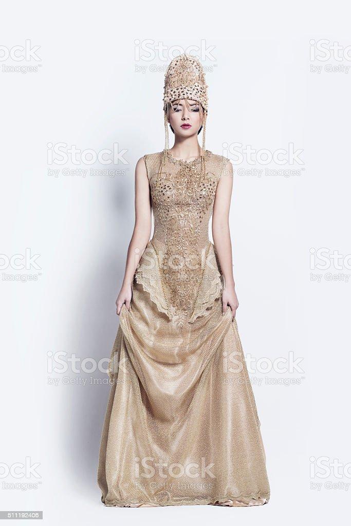 Beautiful woman in golden dress stock photo